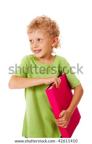 Portrait of smiling young boy holding book - stock photo