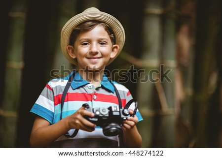 Portrait of smiling young boy in hat holding a camera in park - stock photo