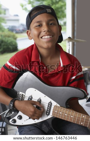Portrait of smiling young boy playing electric guitar in garage - stock photo