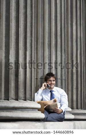 Portrait of smiling young businessman using mobile phone between pillars - stock photo