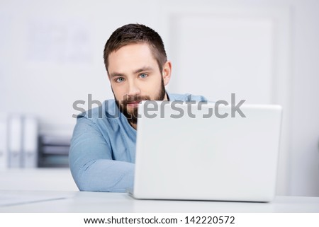 Portrait of smiling young businessman with laptop at desk - stock photo