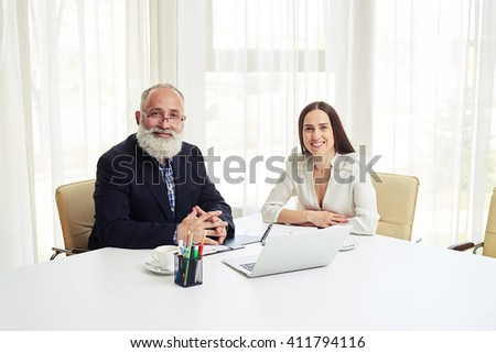 Portrait of smiling young businesswoman and senior man with beard in meeting - stock photo