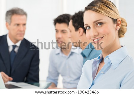 Portrait Of Smiling Young Businesswoman In Front Of Her Colleague - stock photo