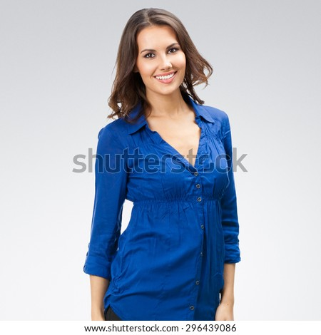 Portrait of smiling young businesswoman, posing at studio against grey background - stock photo