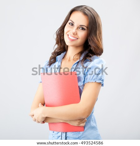 Portrait of smiling young businesswoman with red folder, on grey, with blank copyspace area for advertising slogan or text message. Caucasian brunette model in business concept. Square composition.