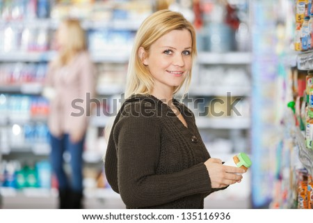 Portrait of smiling young Caucasian woman shopping at supermarket - stock photo
