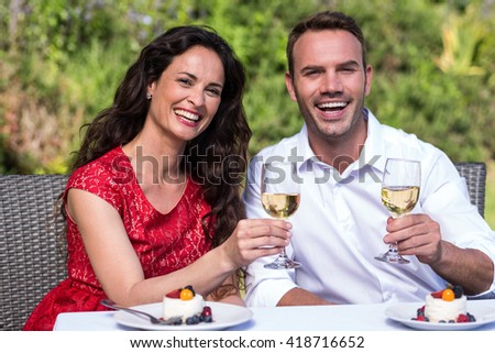 Portrait of smiling young couple holding wineglasses while sitting on chair in lawn - stock photo