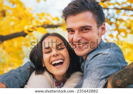 Portrait of smiling young couple outdoors in autumn - stock photo