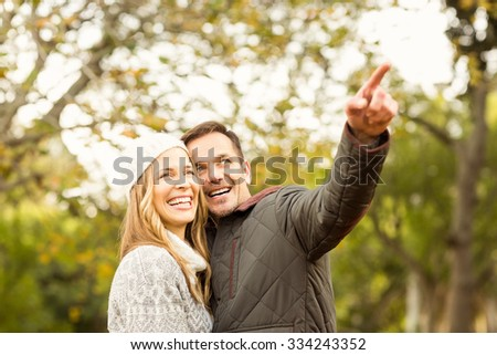 Portrait of smiling young couple pointing something on an autumns day - stock photo