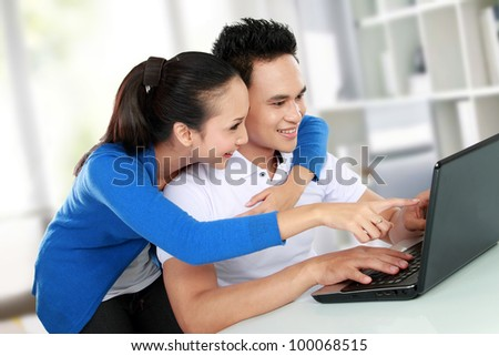 Portrait of smiling young couple using a laptop
