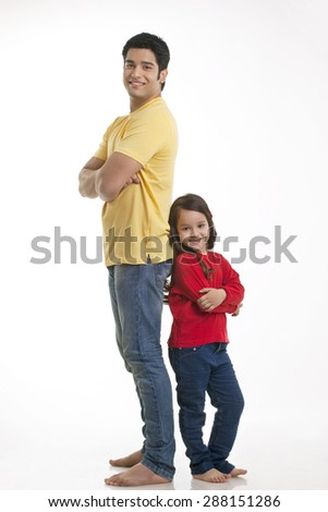 Portrait of smiling young father and daughter standing over white background - stock photo