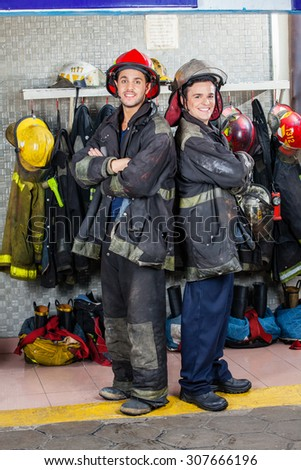 Portrait of smiling young firefighters standing arms crossed at fire station - stock photo