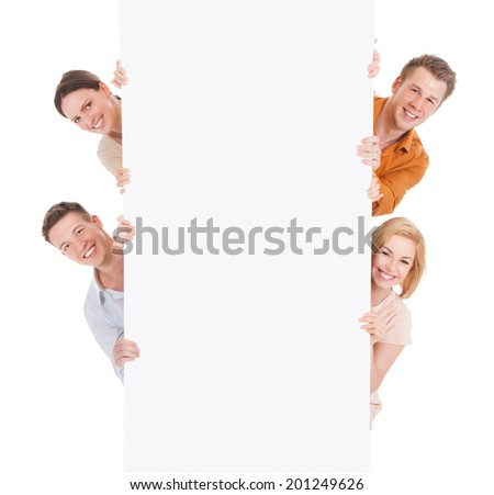 Portrait of smiling young friends looking from behind the blank billboard over white background - stock photo
