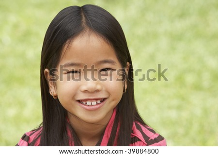Portrait Of Smiling Young Girl Outdoors