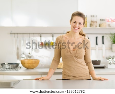 Portrait of smiling young housewife in modern kitchen - stock photo