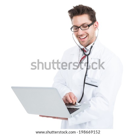 Portrait of smiling young male doctor examining laptop with stethoscope over white background - stock photo