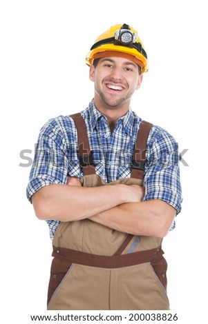 Portrait of smiling young male worker standing arms crossed over white background - stock photo