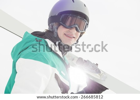 Portrait of smiling young man carrying skis against clear sky - stock photo