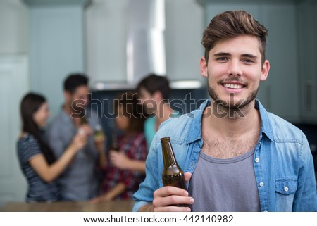 Portrait of smiling young man holding beer bottle while friends enjoying in background - stock photo