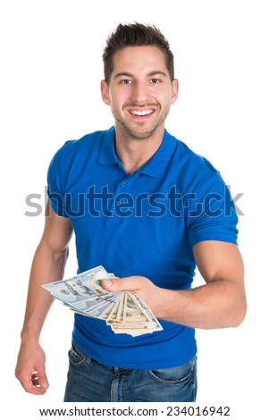 Portrait of smiling young man holding fanned US paper currency isolated over white background - stock photo