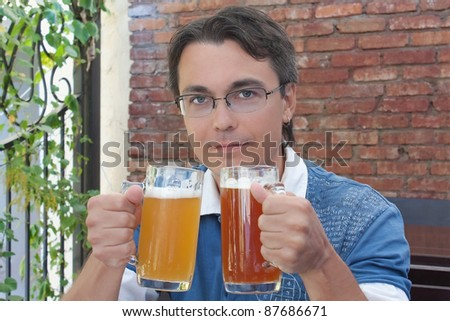 Portrait of smiling young man holding two glasses with beer in pub - stock photo