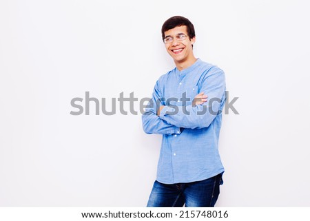 Portrait of smiling young man in glasses and blue shirt with crossed arms on his chest over background - stock photo