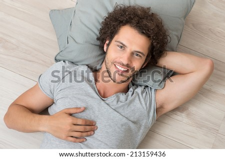 Portrait Of Smiling Young Man Lying On Hardwood Floor Looking At Camera - stock photo