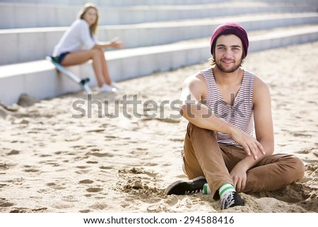 Portrait of smiling young man sitting on sand at beach with woman in background - stock photo