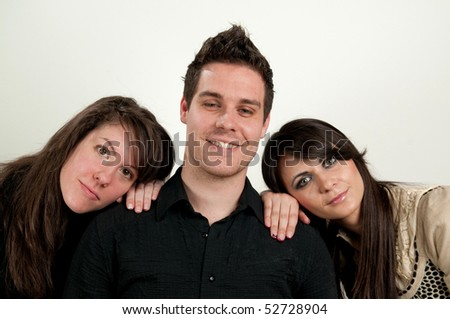 Portrait of smiling young man with two women leaning on shoulder, white background - stock photo