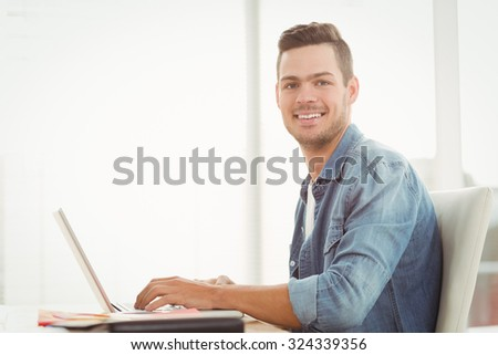 Portrait of smiling young man working on laptop while sitting at desk - stock photo
