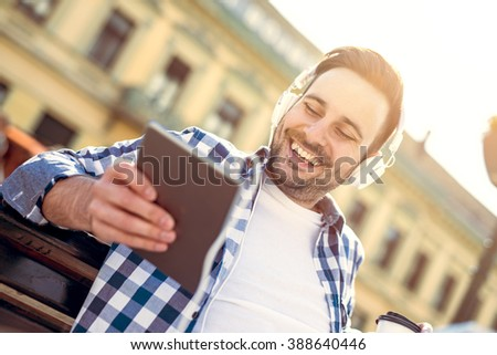Portrait of smiling young man.Young man sitting outdoors listening to music. - stock photo