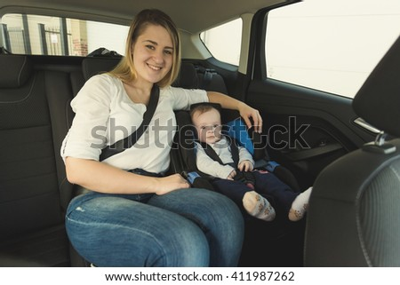 Portrait of smiling young mother and baby boy in car safety seat - stock photo