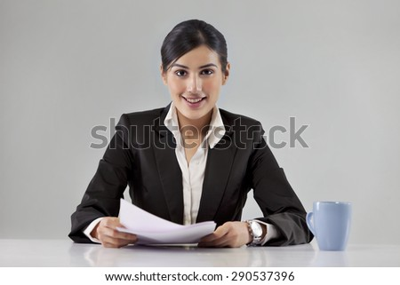 Portrait of smiling young news television host with coffee cup and paper - stock photo