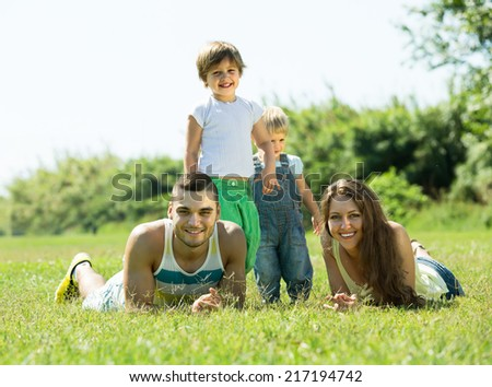 Portrait of smiling young parents with children in grass at park