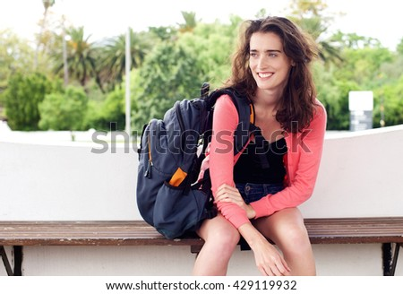 Portrait of smiling young traveler woman sitting on a bench waiting with backpack - stock photo