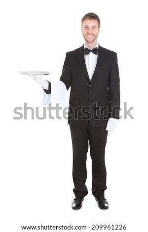 Portrait of smiling young waiter holding empty serving tray isolated over white background - stock photo