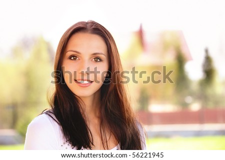 Portrait of smiling young woman against cottage. - stock photo