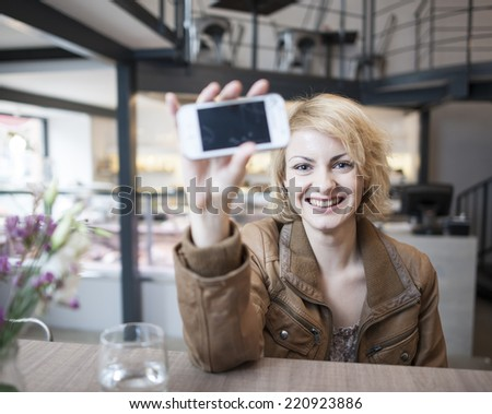 Portrait of smiling young woman displaying cell phone in cafe - stock photo