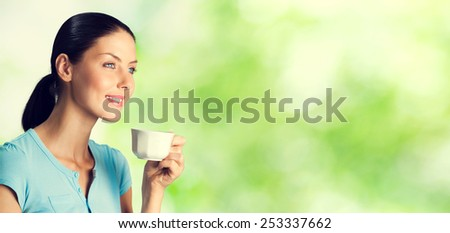 Portrait of smiling young woman drinking coffee, outdoor, with blank copyspace area for text or slogan