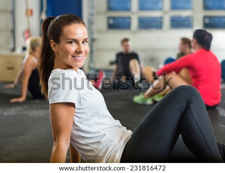 Portrait of smiling young woman exercising in cross training box - stock photo