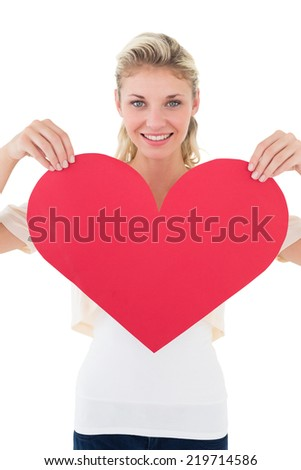 Portrait of smiling young woman holding heart over white background - stock photo