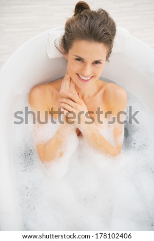 Portrait of smiling young woman in bathtub - stock photo