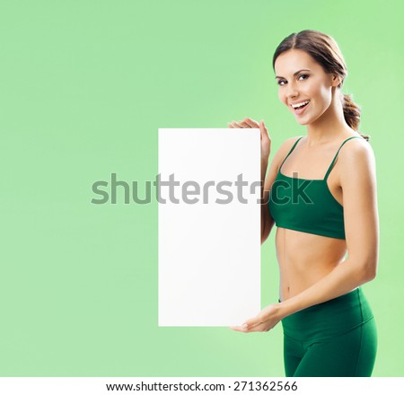 Portrait of smiling young woman in fitness wear showing blank signboard with copyspace area for text or slogan, over green background - stock photo