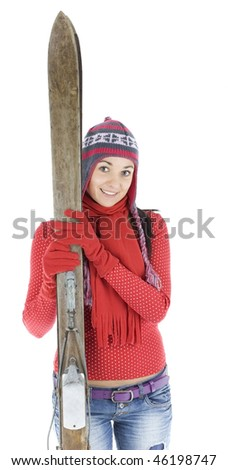 portrait of smiling young woman in winter cap holding old wooden ski - stock photo