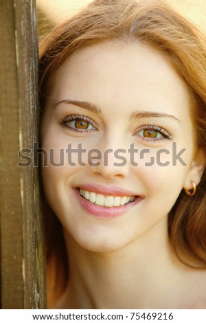 Portrait of smiling young woman, leans about wooden wall