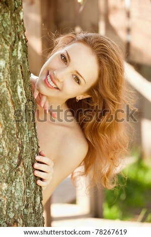 Portrait of smiling young woman looks out because of tree. - stock photo