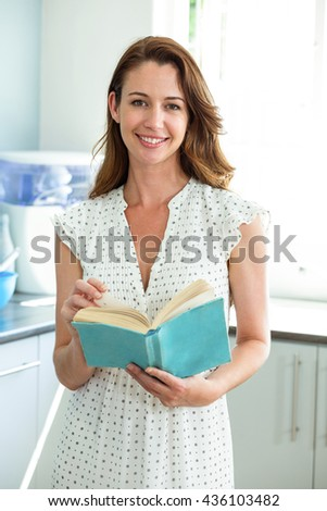 Portrait of smiling young woman reading book in kitchen at home - stock photo