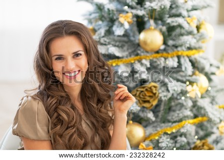 Portrait of smiling young woman sitting near christmas tree - stock photo