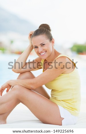 Portrait of smiling young woman sitting on sunbed - stock photo