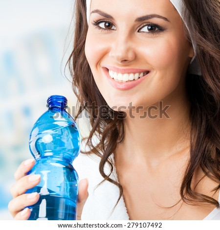 Portrait of smiling young woman with bottle of water, at fitness club or gym - stock photo